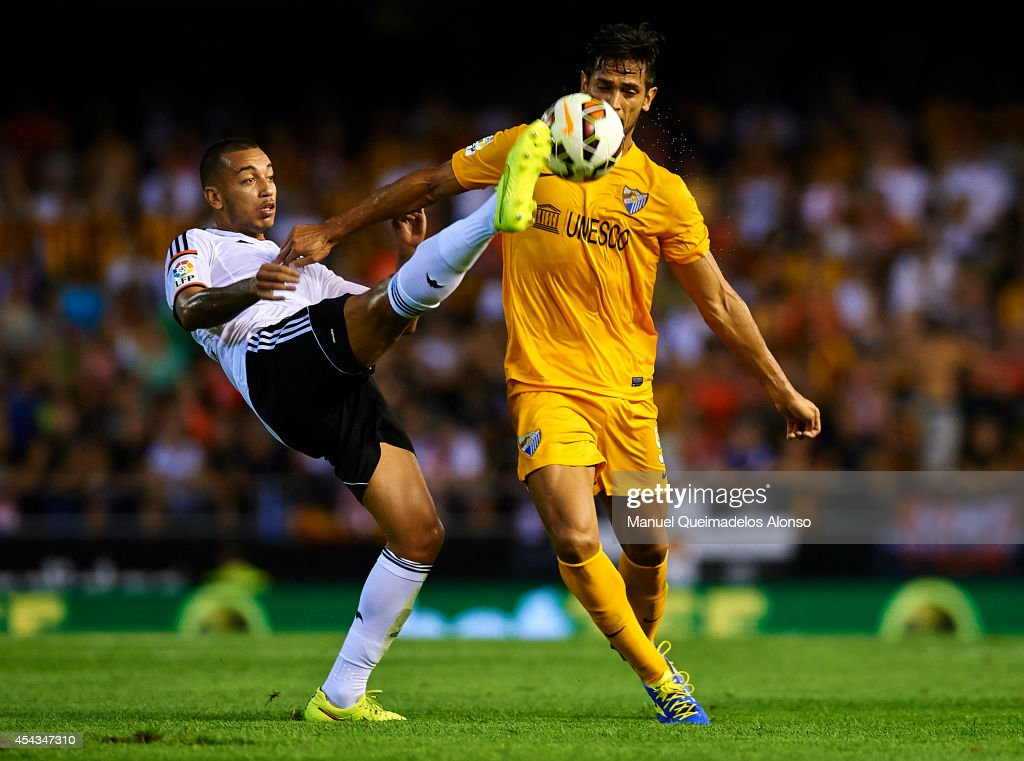 Ruben Vezo of Valencia competes for the ball with Roque Santa Cruz of Malaga during the La Liga match between Valencia CF and Malaga CF at Estadi de...