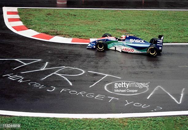 Rubens Barrichello drives the Sasol Jordan Racing Jordan 194 Hart 35 V10 past a sign painted onto the track in rememberance of the late Ayrton Senna...