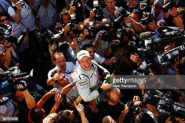 Rubens Barrichello of Brazil and Brawn GP celebrates with team mates in the paddock after winning the Italian Formula One Grand Prix at the Autodromo...