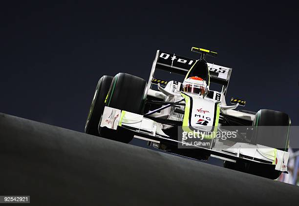 Rubens Barrichello of Brazil and Brawn GP exits the pitlane at dusk during practice for the Abu Dhabi Formula One Grand Prix at the Yas Marina...