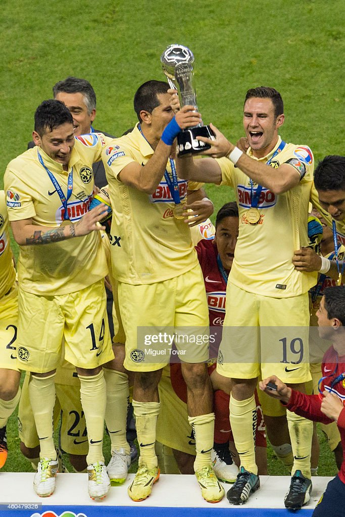 Rubens Sambueza, Jesús Molina and Miguel Layún of America lift the trophy after winning the final second leg match between America and Tigres UANL as part of the Clausura 2014 Liga MX at Azteca Stadium on December 14, 2014 in Mexico City, Mexico.