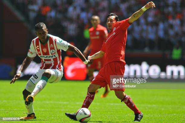 Rubens Sambueza of Toluca vies for the ball with Bryan Beckeles of Necaxa during their Mexican Apertura football tournament match at the Nemesio Diez...