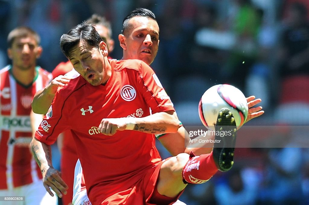 Rubens Sambueza (L) of Toluca vies for the ball with Mario de Luna of Necaxa during their Mexican Apertura football tournament match at the Nemesio Diez stadium in Toluca, Mexico, on August 20, 2017. /