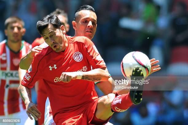 Rubens Sambueza of Toluca vies for the ball with Mario de Luna of Necaxa during their Mexican Apertura football tournament match at the Nemesio Diez...