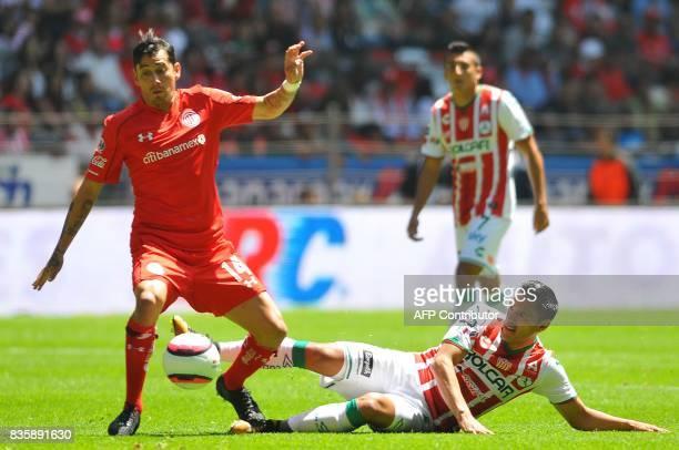 Rubens Sambueza of Toluca vies for the ball with Xavier Baez of Necaxa during their Mexican Apertura football tournament match at the Nemesio Diez...