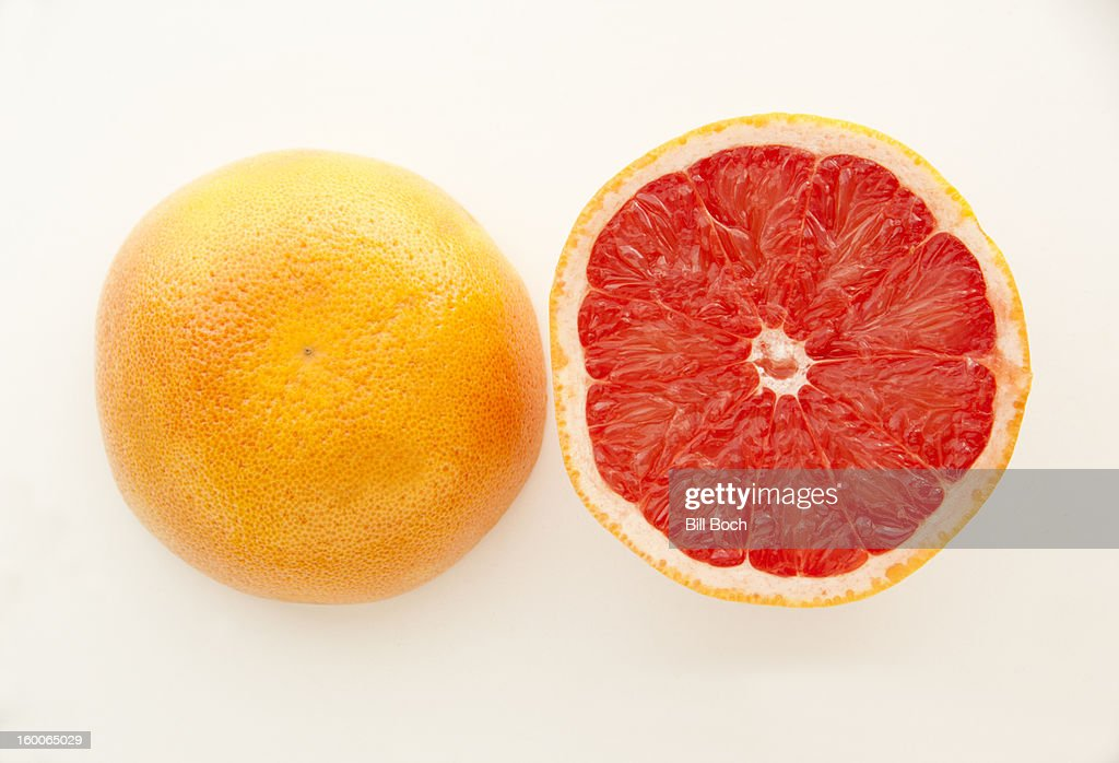 ruby red grapefruit halved on white stock photo