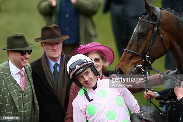 Ruby Walsh celebrates in the winners' enclosure with trainer Willie Mullins and owner Rich Ricci after riding Douvan to victory in the Racing Post...
