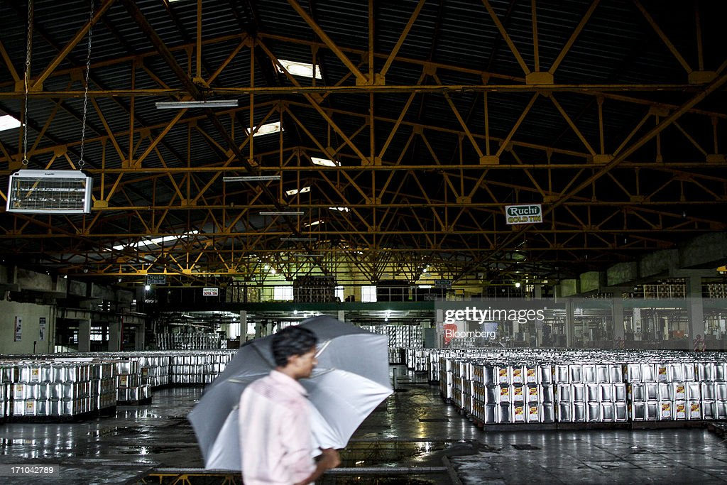 A Ruchi Soya Industries Ltd. employee carries an umbrella as he walks past stacks of 15 liter tins of oil at the Ruchi Soya Industries Ltd. edible oil refinery plant in Patalganga, India, on Tuesday, June 18, 2013. Monsoon, which accounts for 70 percent of Indias annual rainfall, covered the entire country in a record time, accelerating plantings of crops from rice to soybeans and cotton. Rains covered the whole of India by June 16, the earliest ever and ahead of the normal date of July 15, said D.S. Pai, head of the long-range forecasting division at the India Meteorological Department. Photographer: Dhiraj Singh/Bloomberg via Getty Images