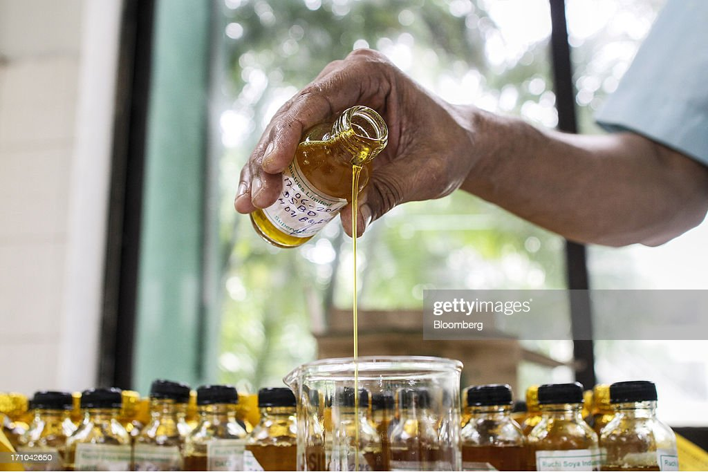 A Ruchi Soya Industries Ltd. employee pours an oil sample into a beaker for analysis in a laboratory of the quality assurance department at the company's edible oil refinery plant in Patalganga, India, on Tuesday, June 18, 2013. Monsoon, which accounts for 70 percent of Indias annual rainfall, covered the entire country in a record time, accelerating plantings of crops from rice to soybeans and cotton. Rains covered the whole of India by June 16, the earliest ever and ahead of the normal date of July 15, said D.S. Pai, head of the long-range forecasting division at the India Meteorological Department. Photographer: Dhiraj Singh/Bloomberg via Getty Images