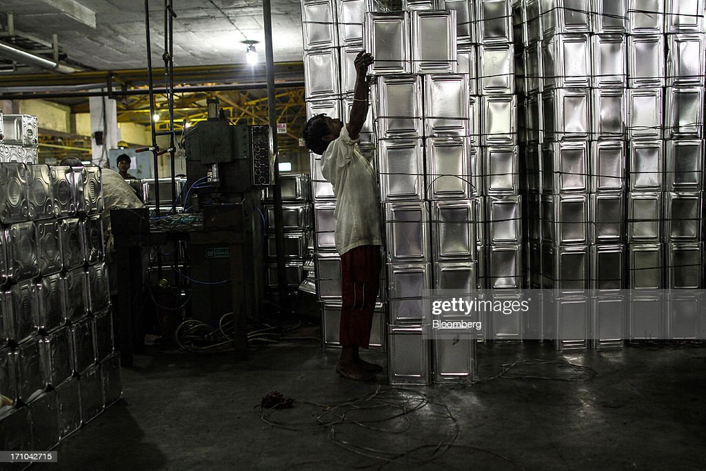 A Ruchi Soya Industries Ltd. employee stacks empty 15 liter oil tin containers in the oil packaging department of the company's edible oil refinery plant in Patalganga, India, on Tuesday, June 18, 2013. Monsoon, which accounts for 70 percent of Indias annual rainfall, covered the entire country in a record time, accelerating plantings of crops from rice to soybeans and cotton. Rains covered the whole of India by June 16, the earliest ever and ahead of the normal date of July 15, said D.S. Pai, head of the long-range forecasting division at the India Meteorological Department. Photographer: Dhiraj Singh/Bloomberg via Getty Images