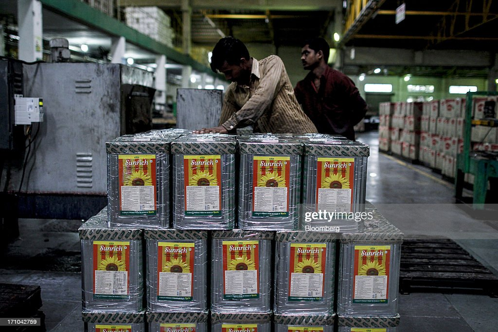 A Ruchi Soya Industries Ltd. employee stacks packaged 15 liter tins of Sunrich refined sunflower oil at the company's edible oil refinery plant in Patalganga, India, on Tuesday, June 18, 2013. Monsoon, which accounts for 70 percent of Indias annual rainfall, covered the entire country in a record time, accelerating plantings of crops from rice to soybeans and cotton. Rains covered the whole of India by June 16, the earliest ever and ahead of the normal date of July 15, said D.S. Pai, head of the long-range forecasting division at the India Meteorological Department. Photographer: Dhiraj Singh/Bloomberg via Getty Images