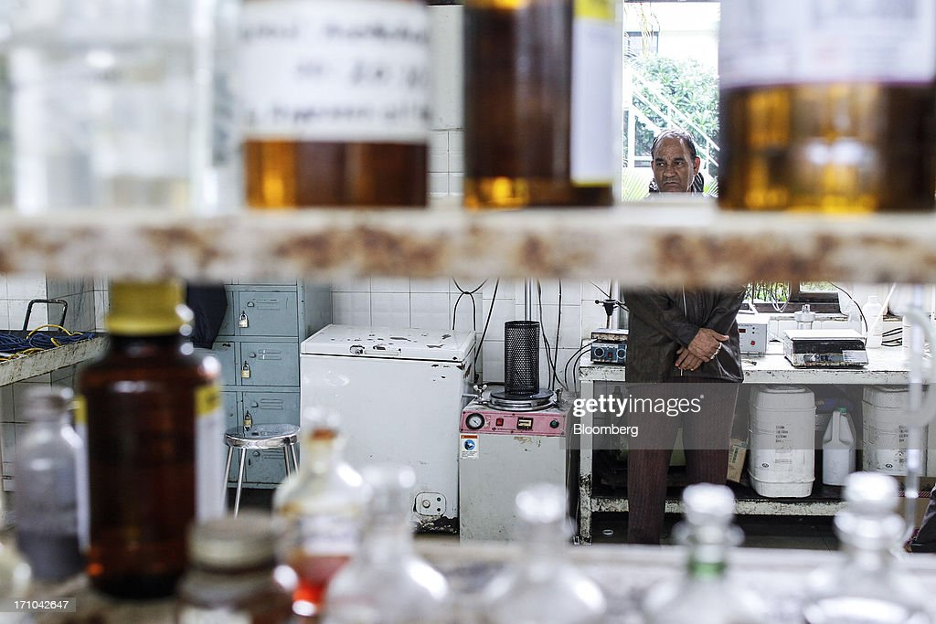 A Ruchi Soya Industries Ltd. employee stands behind bottles of chemicals and oils sitting in a laboratory of the quality assurance department of the company's edible oil refinery plant in Patalganga, India, on Tuesday, June 18, 2013. Monsoon, which accounts for 70 percent of Indias annual rainfall, covered the entire country in a record time, accelerating plantings of crops from rice to soybeans and cotton. Rains covered the whole of India by June 16, the earliest ever and ahead of the normal date of July 15, said D.S. Pai, head of the long-range forecasting division at the India Meteorological Department. Photographer: Dhiraj Singh/Bloomberg via Getty Images