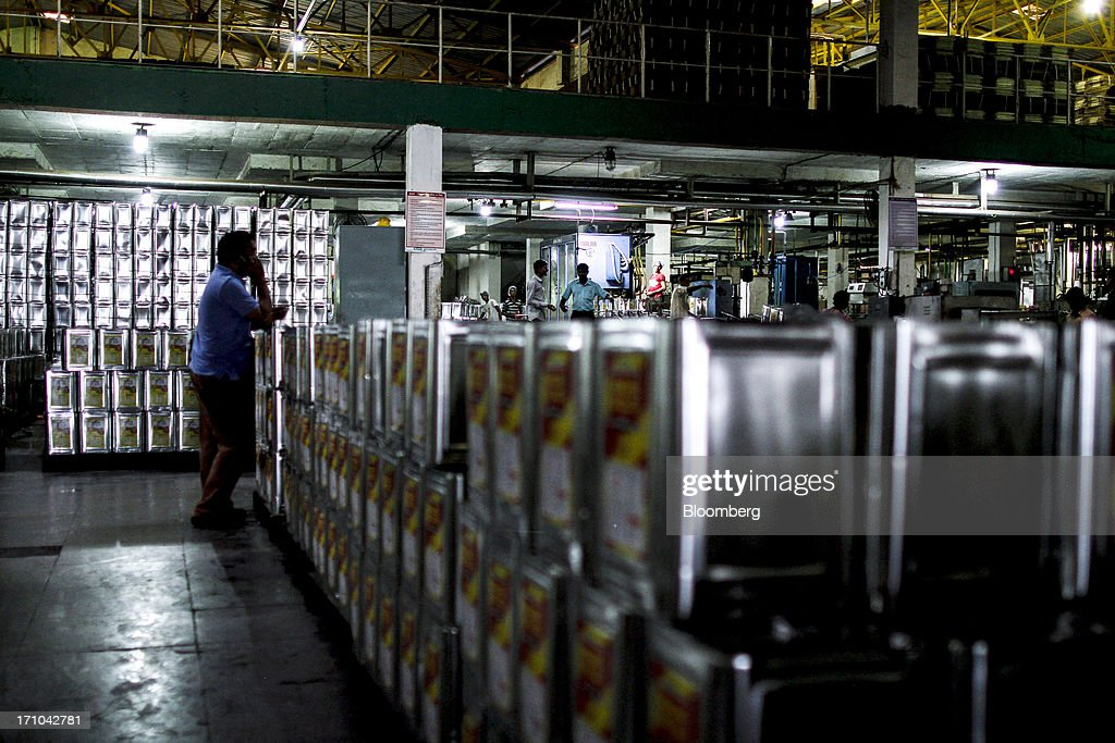 A Ruchi Soya Industries Ltd. employee uses his phone beside stacks of 15 liter tins of oil at the company's edible oil refinery plant in Patalganga, India, on Tuesday, June 18, 2013. Monsoon, which accounts for 70 percent of Indias annual rainfall, covered the entire country in a record time, accelerating plantings of crops from rice to soybeans and cotton. Rains covered the whole of India by June 16, the earliest ever and ahead of the normal date of July 15, said D.S. Pai, head of the long-range forecasting division at the India Meteorological Department. Photographer: Dhiraj Singh/Bloomberg via Getty Images