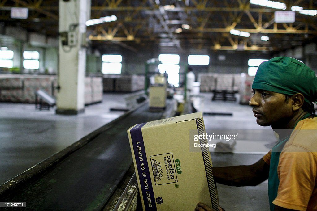 A Ruchi Soya Industries Ltd. employee waits to seal a box of one litre packs of Sunrich refined sunflower oil at the company's edible oil refinery plant in Patalganga, India, on Tuesday, June 18, 2013. Monsoon, which accounts for 70 percent of Indias annual rainfall, covered the entire country in a record time, accelerating plantings of crops from rice to soybeans and cotton. Rains covered the whole of India by June 16, the earliest ever and ahead of the normal date of July 15, said D.S. Pai, head of the long-range forecasting division at the India Meteorological Department. Photographer: Dhiraj Singh/Bloomberg via Getty Images