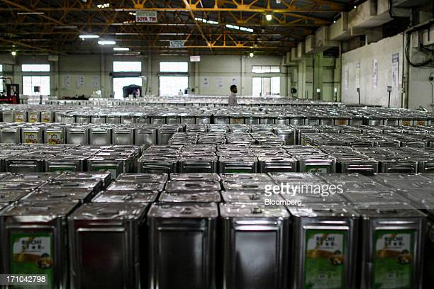 A Ruchi Soya Industries Ltd employee walks between stacks of 15 liter tins of oil at the Ruchi Soya Industries Ltd edible oil refinery plant in...