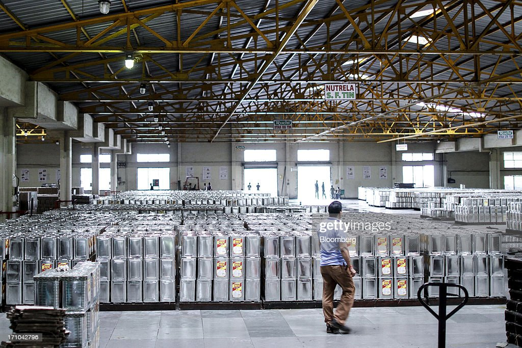 A Ruchi Soya Industries Ltd. employee walks past stacks of 15 liter tins of oil at the Ruchi Soya Industries Ltd. edible oil refinery plant in Patalganga, India, on Tuesday, June 18, 2013. Monsoon, which accounts for 70 percent of Indias annual rainfall, covered the entire country in a record time, accelerating plantings of crops from rice to soybeans and cotton. Rains covered the whole of India by June 16, the earliest ever and ahead of the normal date of July 15, said D.S. Pai, head of the long-range forecasting division at the India Meteorological Department. Photographer: Dhiraj Singh/Bloomberg via Getty Images