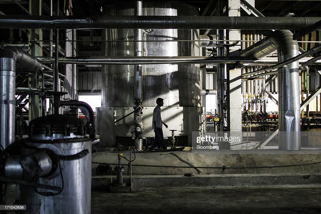 A Ruchi Soya Industries Ltd. employee walks through unit 2 of the vanaspati oil manufacturing department at the company's edible oil refinery plant in Patalganga, India, on Tuesday, June 18, 2013. Monsoon, which accounts for 70 percent of Indias annual rainfall, covered the entire country in a record time, accelerating plantings of crops from rice to soybeans and cotton. Rains covered the whole of India by June 16, the earliest ever and ahead of the normal date of July 15, said D.S. Pai, head of the long-range forecasting division at the India Meteorological Department. Photographer: Dhiraj Singh/Bloomberg via Getty Images