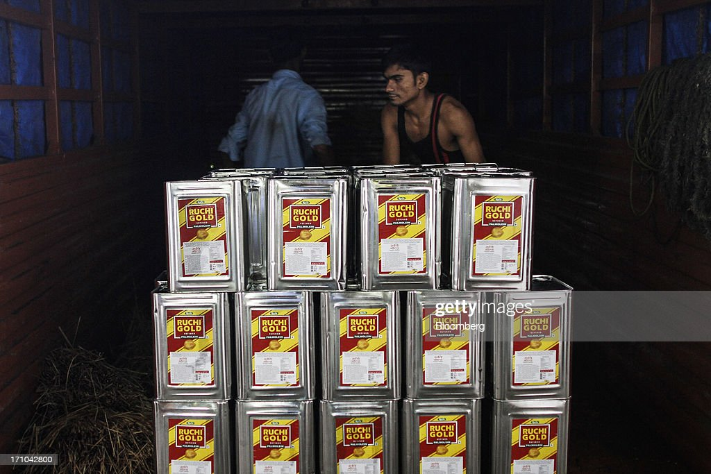 Ruchi Soya Industries Ltd. employees load a truck with 15 liter tins of Ruchi Gold refined palmolein oil at the company's edible oil refinery plant in Patalganga, India, on Tuesday, June 18, 2013. Monsoon, which accounts for 70 percent of Indias annual rainfall, covered the entire country in a record time, accelerating plantings of crops from rice to soybeans and cotton. Rains covered the whole of India by June 16, the earliest ever and ahead of the normal date of July 15, said D.S. Pai, head of the long-range forecasting division at the India Meteorological Department. Photographer: Dhiraj Singh/Bloomberg via Getty Images