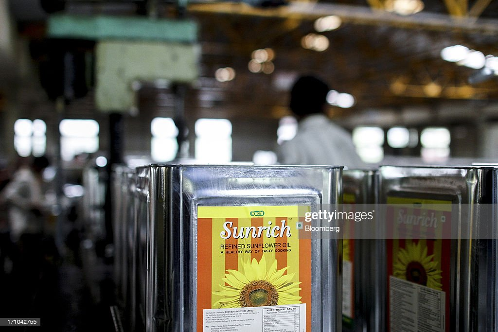 Ruchi Soya Industries Ltd.'s 15 liter tins of Sunrich refined sunflower oil sit waiting to be sealed at the company's edible oil refinery plant in Patalganga, India, on Tuesday, June 18, 2013. Monsoon, which accounts for 70 percent of Indias annual rainfall, covered the entire country in a record time, accelerating plantings of crops from rice to soybeans and cotton. Rains covered the whole of India by June 16, the earliest ever and ahead of the normal date of July 15, said D.S. Pai, head of the long-range forecasting division at the India Meteorological Department. Photographer: Dhiraj Singh/Bloomberg via Getty Images