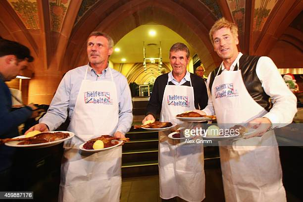 Rudi Bommer Friedhelm Funkel and Uli Stein serve food during the christmas goose lunch for homeless people at Ratskeller on December 3 2014 in...
