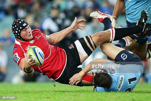 Rudi Mathee of the Lions offloads the ball in a tackle during the round 14 Super Rugby match between the Waratahs and the Lions at Allianz Stadium on...