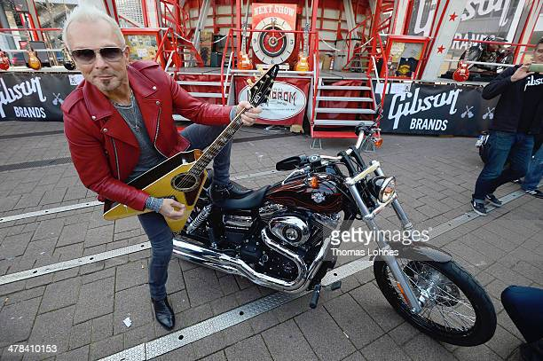 Rudolf Schenker guitar player of the band Scorpions poses with a 'Gibson Custom Acoustic Flying V' in front of a Harley Davidson motorcycle at...