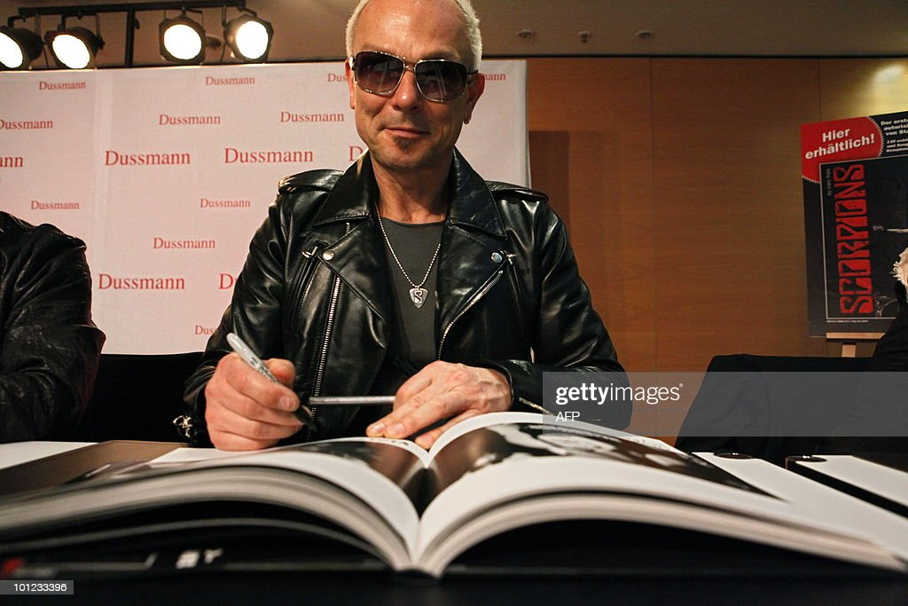 Rudolf Schenker of the German rock band Scorpions signs books for fans after a press conference on May 28, 2010 at the Dussmann bookshop in Berlin during the presentation of a new coffee-table book by photographer Marc Theis. The photographer accompanied the band on their world tour from 2007 to 2009.