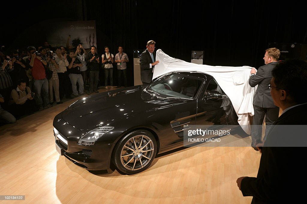 Rudy Borgenheimer, (L), president and CEO of Mercedez-Benz Indonesia and Roland Staehler, (R), sales and marketing director unveil the new Mercedes-Benz SLS AMG during the launching of the 6.3 liter V8 front-mid-engine luxury sports car in Jakarta on June 16, 2010.