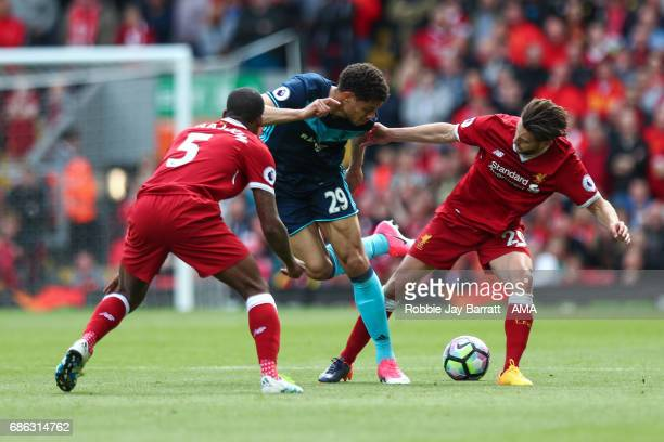 Rudy Gestede of Middlesbrough and Adam Lallana of Liverpool during the Premier League match between Liverpool and Middlesbrough at Anfield on May 21...