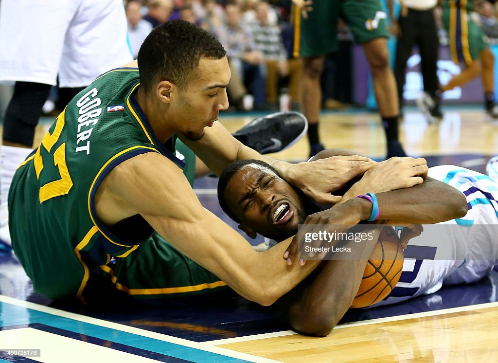 Rudy Gobert #27 of the Utah Jazz and Michael Kidd-Gilchrist #14 of the Charlotte Hornets battle for a loose ball during their game at Time Warner Cable Arena on December 20, 2014 in Charlotte, North Carolina.