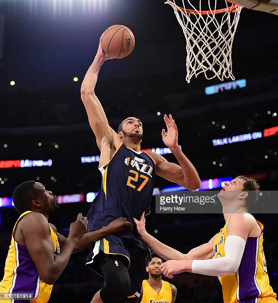 Rudy Gobert of the Utah Jazz dunks between Timofey Mozgov and Luol Deng of the Los Angeles Lakers at Staples Center on December 5 2016 in Los Angeles...