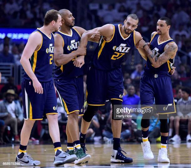 Rudy Gobert of the Utah Jazz is helped off the court by Joe Ingles Boris Diaw and George Hill after an injury during the first half against the LA...