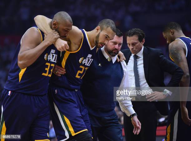 Rudy Gobert of the Utah Jazz is helped off the court past head coach Quin Snyder by Boris Diaw and medical staff during the first half against the LA...