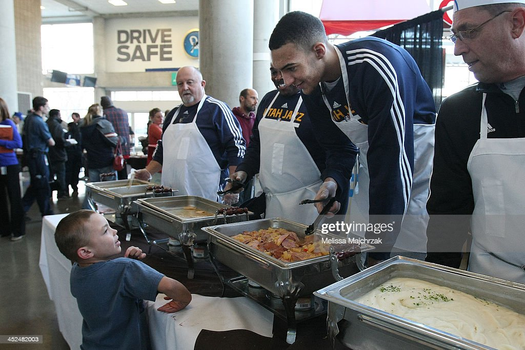 Rudy Gobert #27 of the Utah Jazz talks with a young fan during the we care-we share Thanksgiving Dinner feeding the homeless at EnergySolutions Arena on November 27, 2013 in Salt Lake City, Utah.