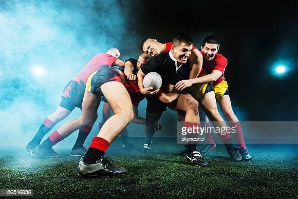 Rugby action at night.