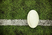 Above view of a rugby ball on a grass on the white line.