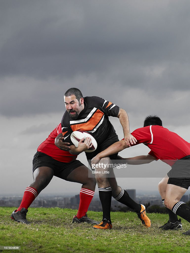 Rugby evades two tacklers. : Stock Photo