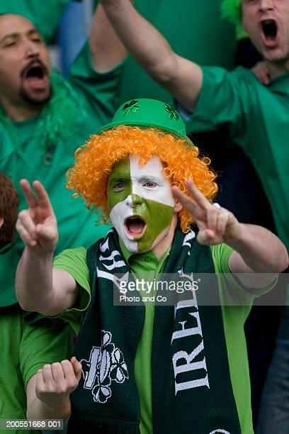 Rugby fan wearing wig with Ireland flag painted on face, cheering