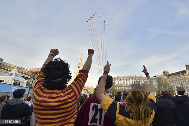 Rugby fans cheer from a fanzone in Trafalgar Square as the Red Arrows fly past before the start of the final match of the 2015 Rugby World Cup...