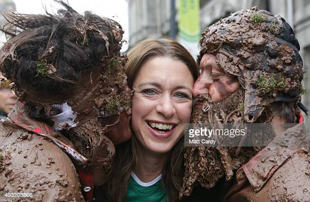 Rugby fans dressed as muddy players kiss a spectactor as they pose for a photograph close to the Millennium Stadium where Ireland are playing...