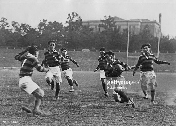 A rugby match between Keio University and Hitotsubashi University at the Meiji Shrine ground in Tokyo Japan circa 1932 Keio won the game with a score...