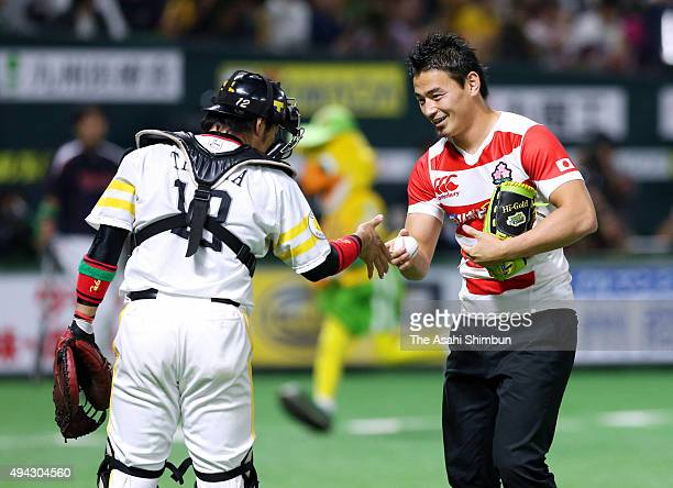 Rugby player Ayumu Goromaru receives the ball from catcher Hiroaki Takaya of SoftBank Hawks after the memorial first pitch prior to the baseball...