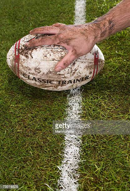 Rugby player grabbing ball on sports field, close-up of hand