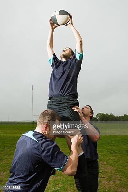 Joueur de Rugby à sauter pour attraper le ballon en ligne de touche, soutenu