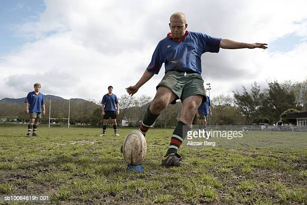 Rugby player kicking ball on sports field, low angle view