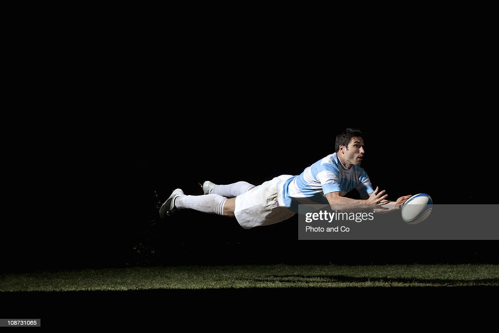 Rugby player making a diving pass of the ball : Stock Photo