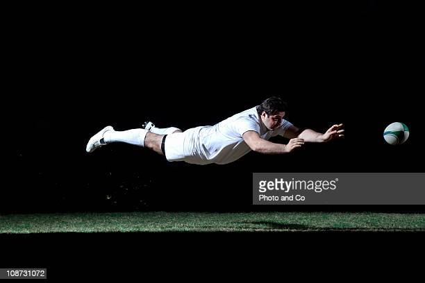 Rugby player making a diving pass of the ball