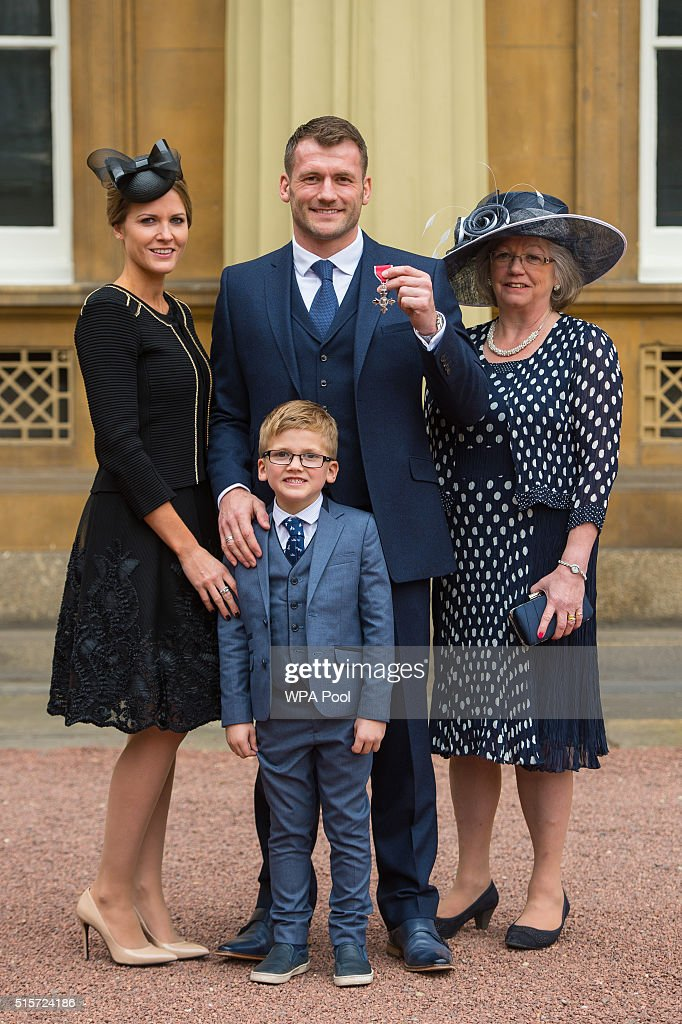 Rugby player Mark Cueto with wife Suzie, son Max and mother Anne as he holds his Member of the British Empire (MBE) medal which was awarded by the Duke of Cambridge at an investiture ceremony at Buckingham Palace on March 15, 2015 in London, England.