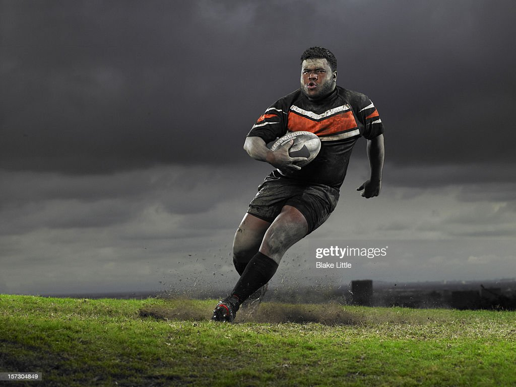 Rugby player running with ball.