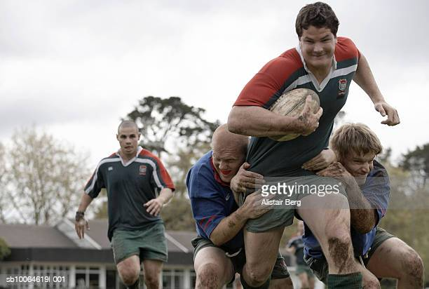 Rugby player running with ball through tackle, low angle view